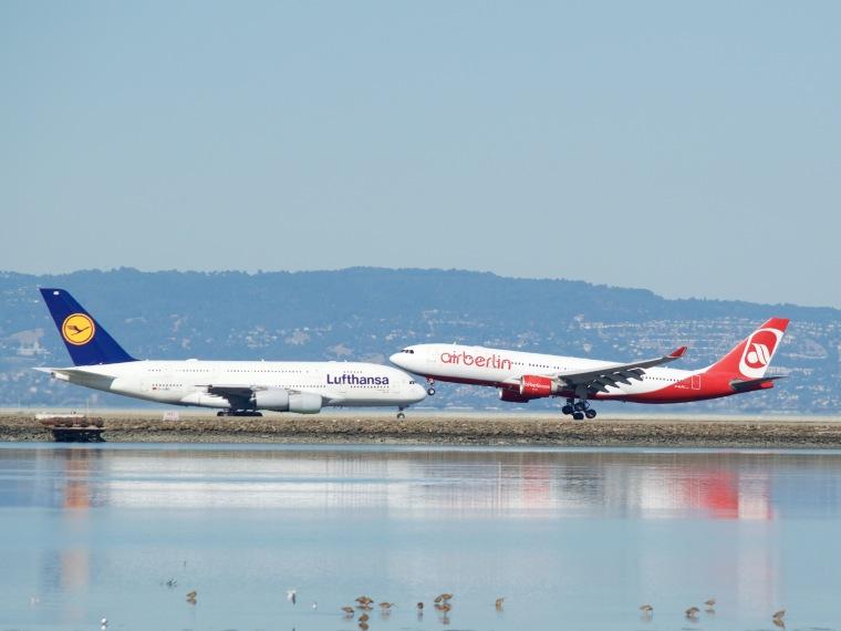 Air_Berlin_A-330_landing_Lufthansa_Airbus_A-380_taxiing_to_takeoff_runway_28_SFO_(30144412484)